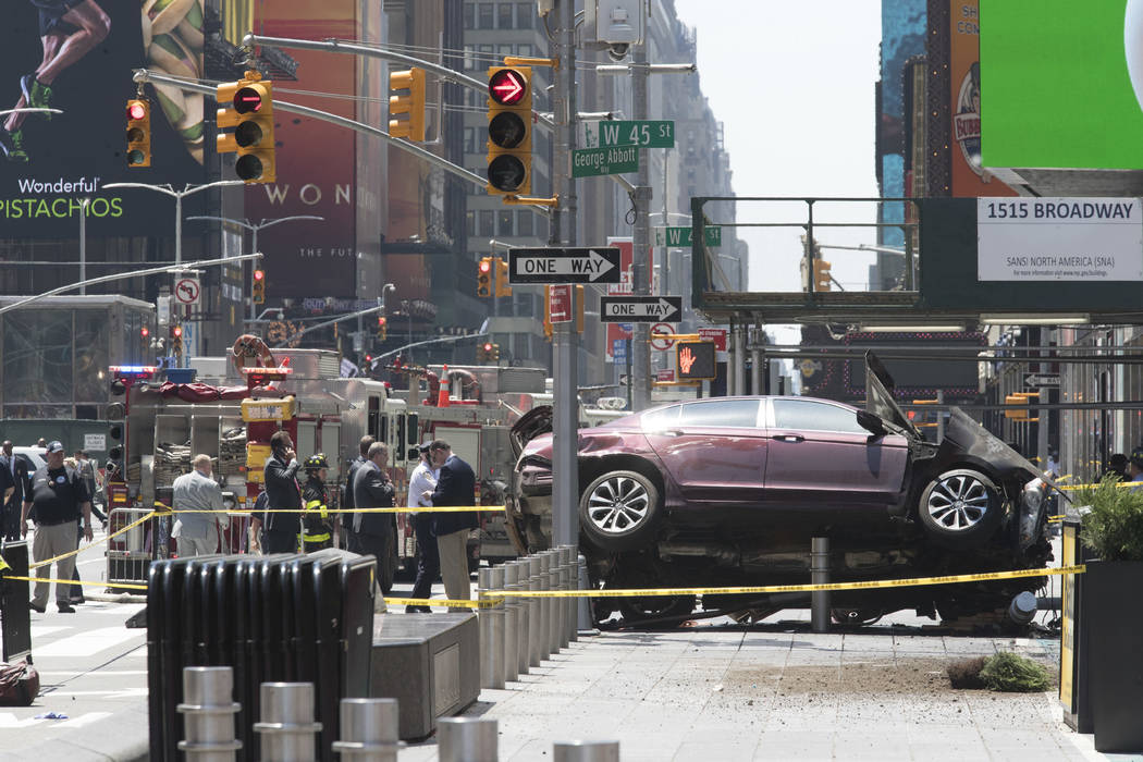 A car rests on a security barrier in New York's Times Square after driving through a crowd of pedestrians May 18, 2017, injuring at least a dozen people. (Mary Altaffer/File, AP)
