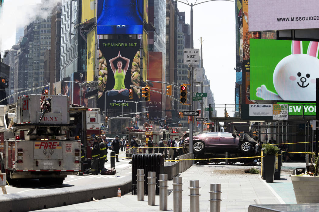 A car rests on a security barrier in New York's Times Square on Thursday, May 18, 2017, after driving through a crowd of pedestrians, injuring at least a dozen people. A three-foot-tall piece of s ...