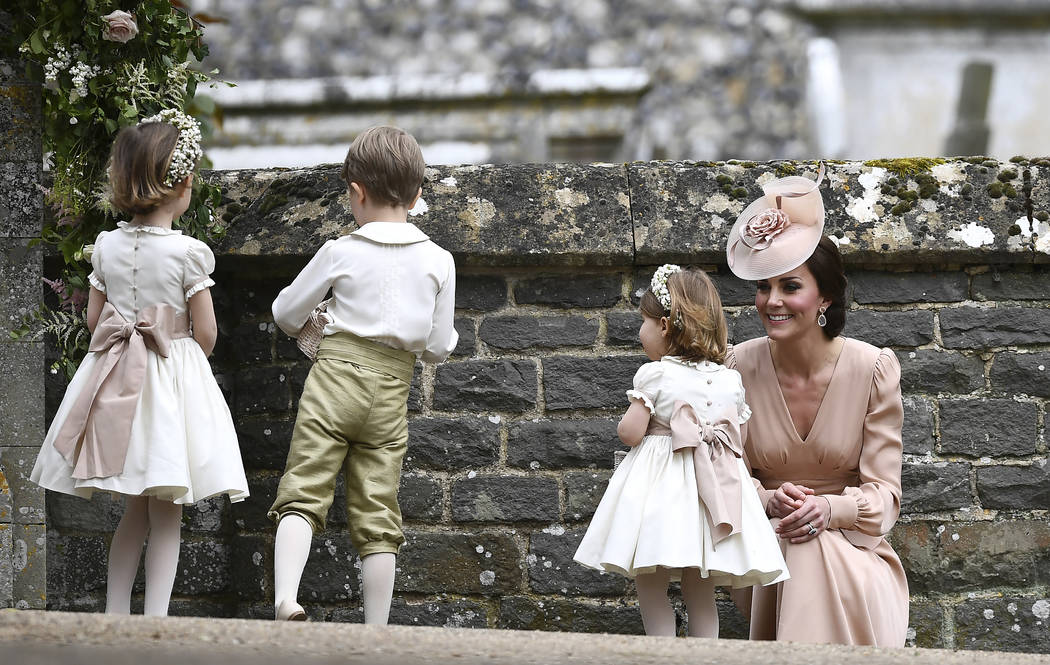 Kate, the Duchess of Cambridge, right, smiles at her daughter Princess Charlotte, after the wedding of her sister Pippa Middleton to James Matthews, at St Mark's Church in Englefield, England Satu ...