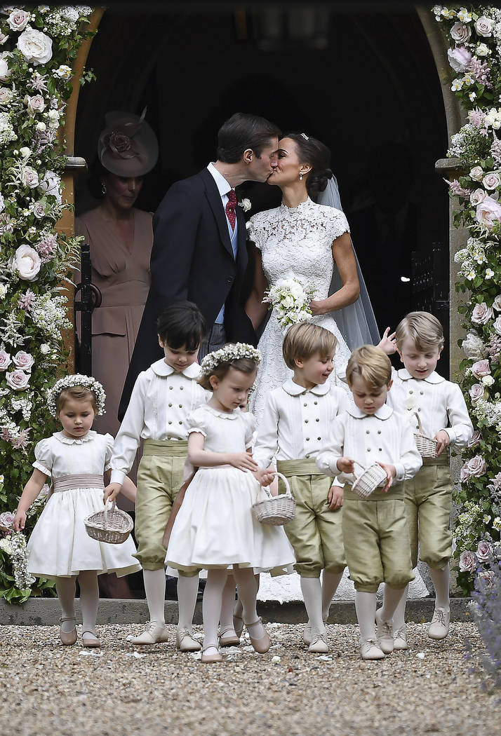 Pippa Middleton, background right, kisses James Matthews after their wedding at St Mark's Church in Englefield, England, Saturday, May 20, 2017. Middleton, the sister of Kate, Duchess of Cambridge ...