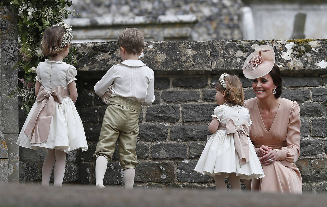 Kate, Duchess of Cambridge, right, smiles as she kneels next to her children Princess Charlotte, second right, and Prince George, who were flower boys and girls at the wedding of Pippa Middleton a ...