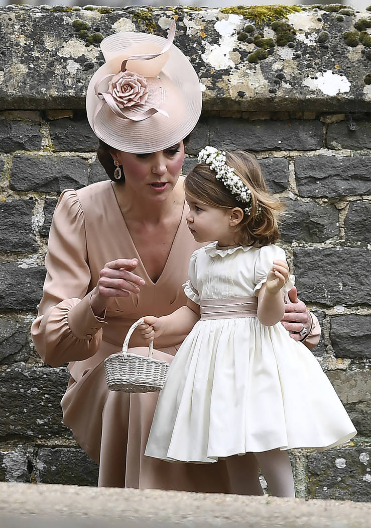 Kate, the Duchess of Cambridge, talks to her daughter Princess Charlotte, after the wedding of her sister Pippa Middleton to James Matthews, at St Mark's Church in Englefield, England Saturday, Ma ...