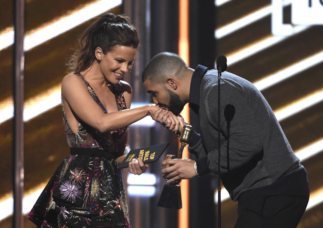 Drake kisses presenter Kate Beckinsale's hand as he walks on stage to accepts the award for top male artist at the Billboard Music Awards at the T-Mobile Arena on Sunday, May 21, 2017, in Las Vega ...