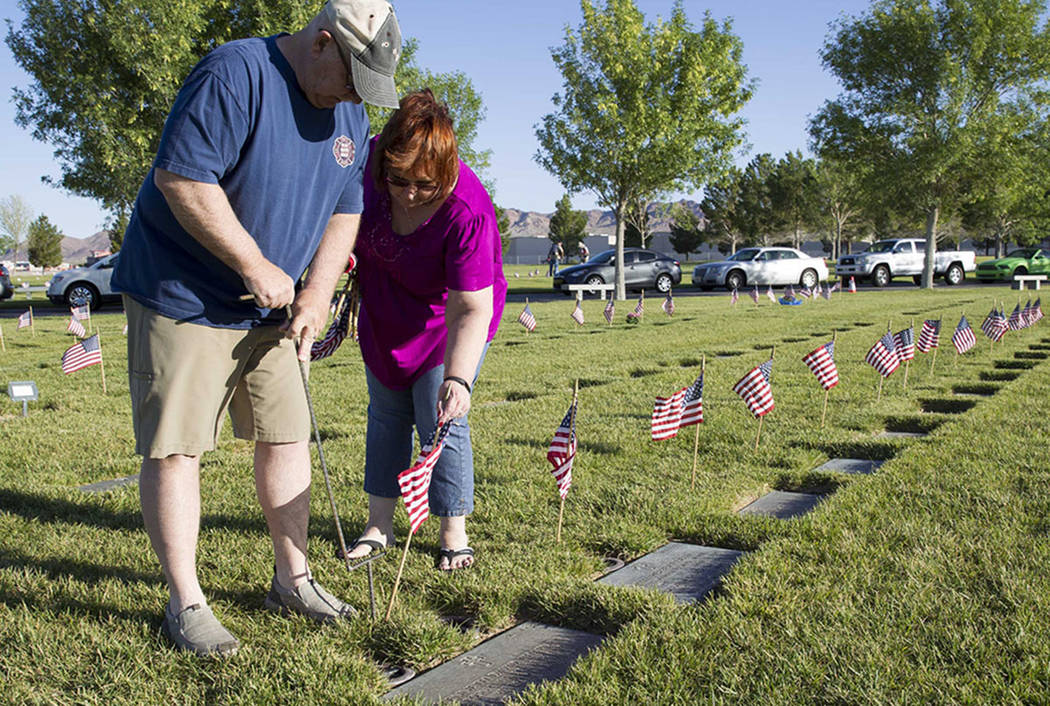 Henderson residents Kevin Morsey and his wife Kathy Morsey assist with the process of placing American flags at the headstones of U.S. military personnel buried at the Southern Nevada Veterans Cem ...