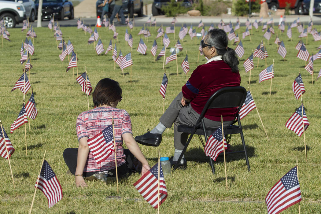 Two women visit the headstone of U.S. military personnel buried at the Southern Nevada Veterans Cemetery in Boulder City on Saturday, May 27, 2017. Richard Brian Las Vegas Review-Journal @vegaspho ...