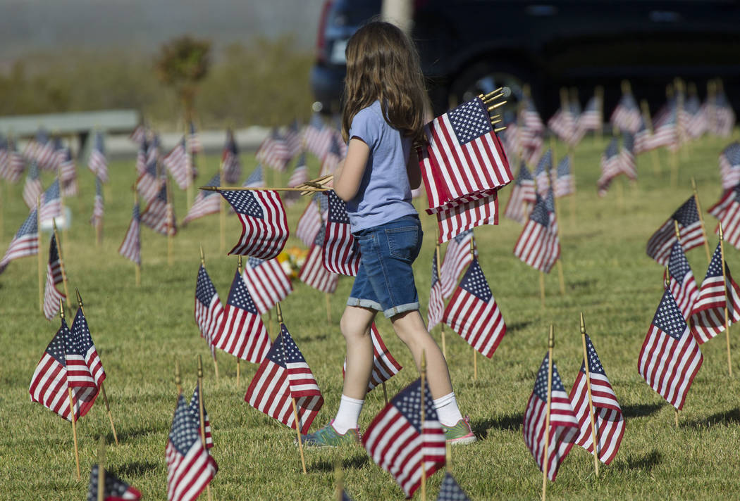 A young girl assists with the process of placing flags at the headstones of U.S. military personnel buried at the Southern Nevada Veterans Cemetery in preparation for Memorial Day in Boulder City, ...