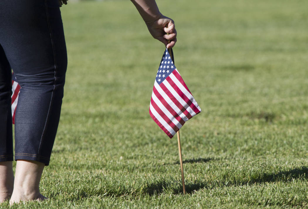 A woman places an American flag at the headstone of U.S. military personnel buried at the Southern Nevada Veterans Cemetery in preparation for Memorial Day in Boulder City on Saturday, May 27, 201 ...