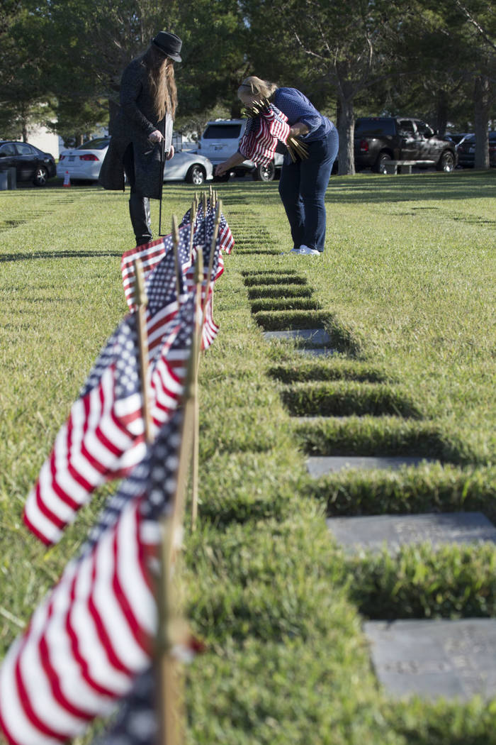 Volunteers assist with the process of placing American flags at the headstones of U.S. military personnel buried at the Southern Nevada Veterans Cemetery in preparation for Memorial Day in Boulder ...