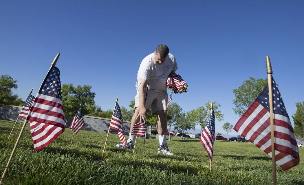 Henderson resident Jim Payne assists with the process of placing American flags at the headstones of U.S. military personnel buried at the Southern Nevada Veterans Cemetery in preparation for Memo ...