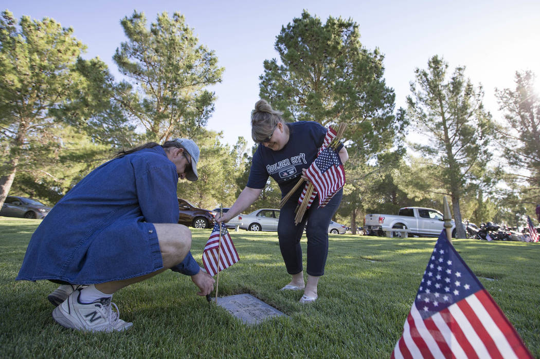 Boulder City residents R.J. Cornwell, left, and Kimberly Vitto assists with the process of placing American flags at the headstones of U.S. military personnel buried at the Southern Nevada Veteran ...