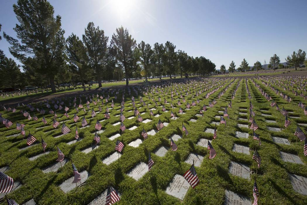 American flags at the headstones of U.S. military personnel buried at the Southern Nevada Veterans Cemetery in preparation for Memorial Day in Boulder City on Saturday, May 27, 2017. Richard Brian ...