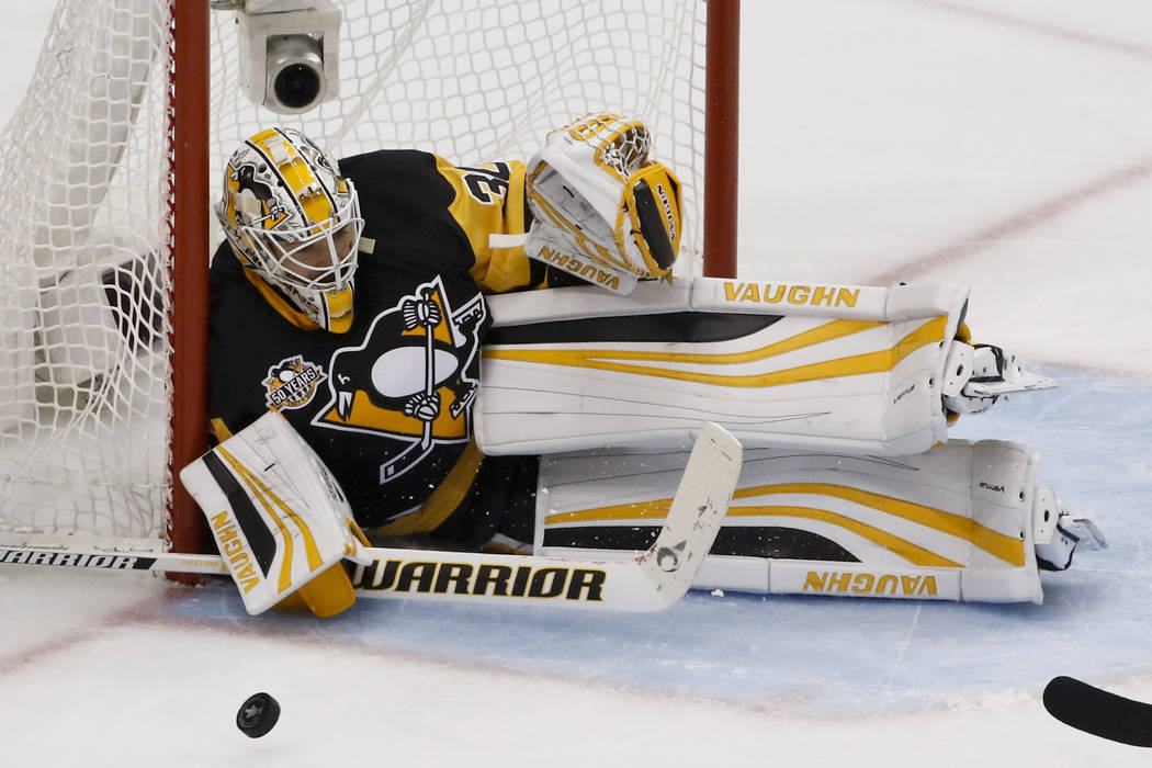 The puck slides past Pittsburgh Penguins goalie Matt Murray (30) as he plays against the Ottawa Senators during the first period of Game 5 in the NHL hockey Stanley Cup Eastern Conference finals, ...