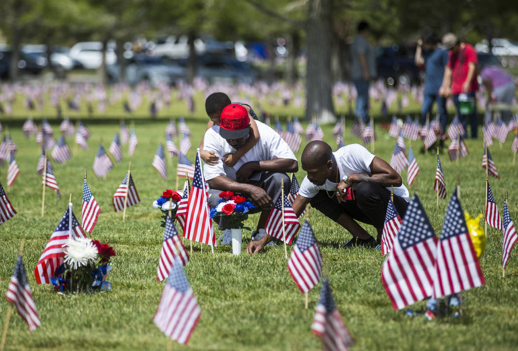 Antwoyne Wilson, left, with son AJ Wilson, 5, on his shoulders, and Kory Lavoll place flowers at the grave of their father, James Edward Wilson, at the Southern Nevada Veterans Memorial Cemetery i ...