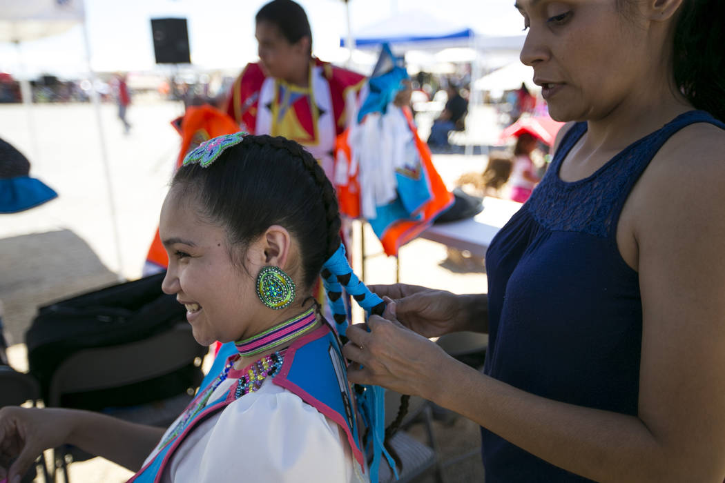 Aiyana Rubio, 15, get helps with her hair by her mother, Vanessa Rubio, before the start of the grand entry ceremonies during the 28th annual Snow Mountain Pow Wow on Saturday, May 27, 2017. Richa ...