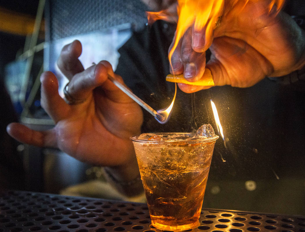 Aria bartender Darren West lights a burnt orange cocktail during For the Love of Cocktails charity event for breast cancer on Friday, May 19, 2017, at Skyfall Lounge, at the Delano hotel-casino, i ...
