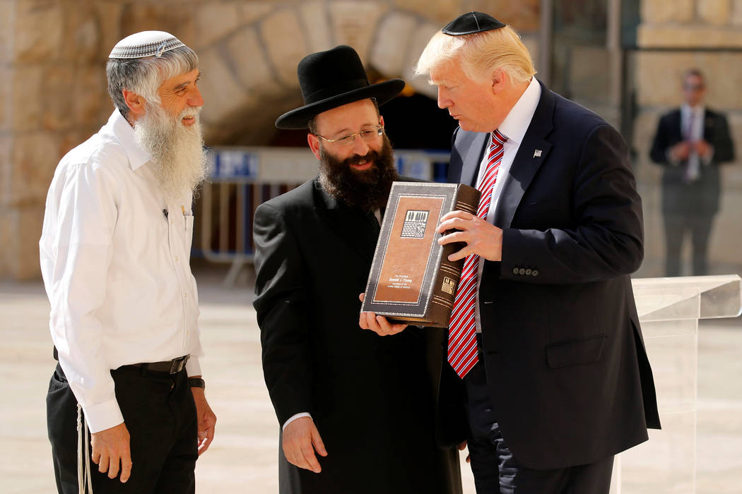 U.S. President Donald Trump (R) receives a gift of a book of Psalms from Western Wall Heritage Foundation Director General Mordechai Elias (L) and Rabbi of the Western Wall Shmuel Rabinovitch (C)  ...