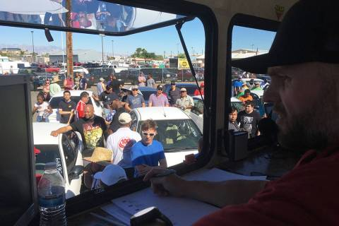 TNT Auction owner and chief auctioneer Mike McKee drives up the bid price on a vehicle. (Brian ...