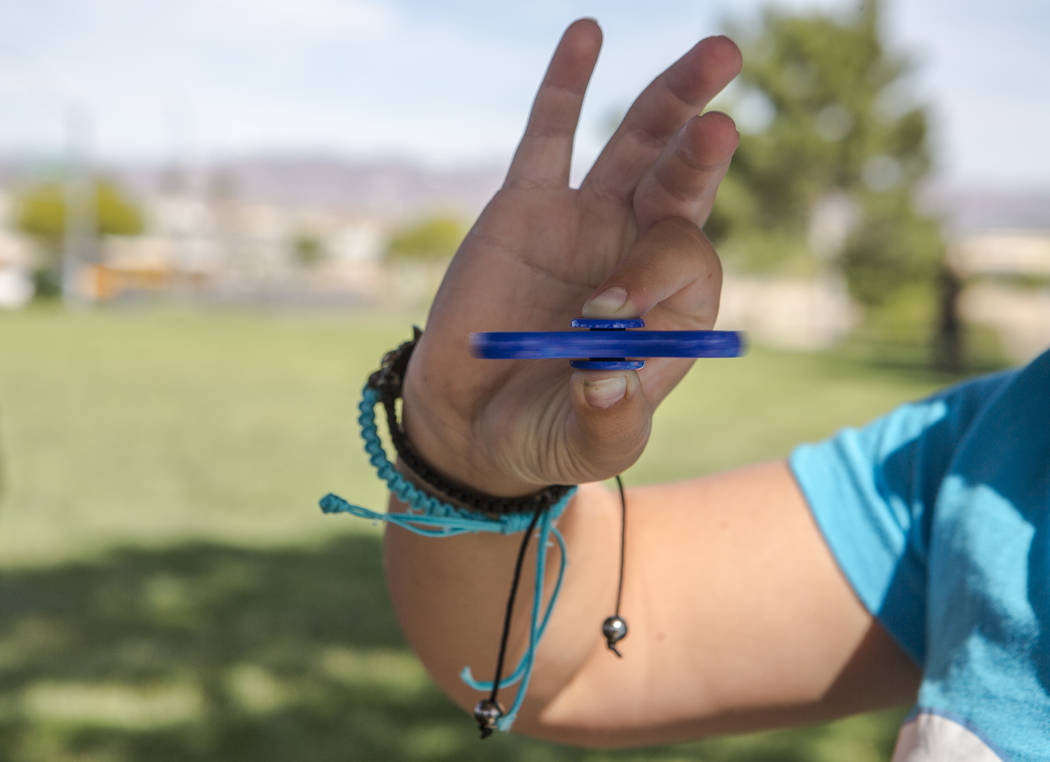 Tayler Rexroad, 8, plays with her fidget spinner at Stephanie Lynn Craig Park in Henderson on Monday, May 22, 2017. Fidget spinners have been the source of scrutiny by some school teachers and off ...