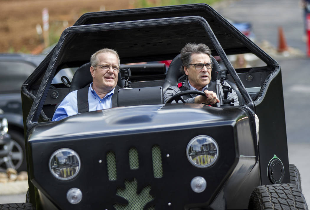 Energy Secretary Rick Perry, right, drives a 3-D printed vehicle at Oak Ridge National Laboratory's Manufacturing Demonstration Facility with staffer Craig Blue in Knoxville, Tenn., Monday, May 22 ...