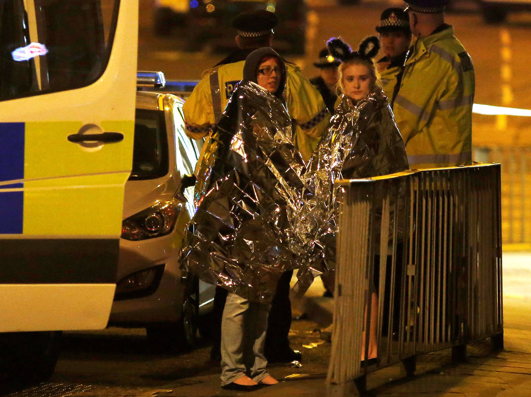 Two women wrapped in thermal blankets stand near the Manchester Arena, where U.S. singer Ariana Grande had been performing, in Manchester, northern England, Britain, May 23, 2017. (Andrew Yates/Re ...