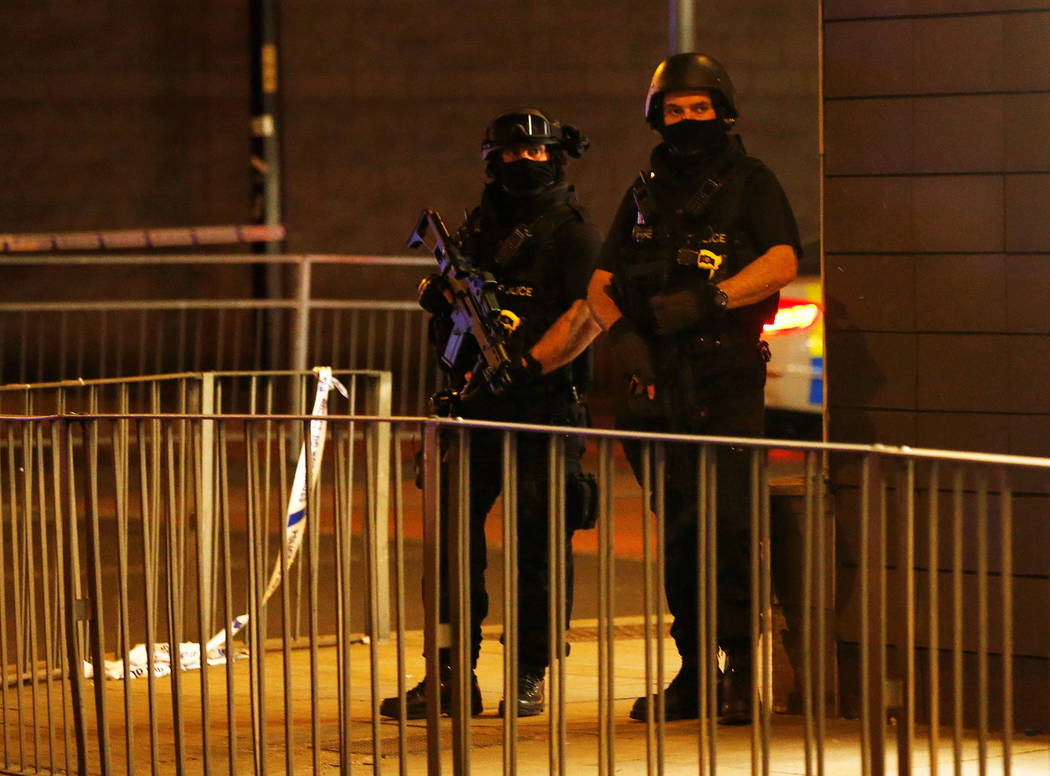 Armed police officers stand next to a police cordon outside the Manchester Arena, where U.S. singer Ariana Grande had been performing, in Manchester, northern England, Britain, May 23, 2017. (Reuters)