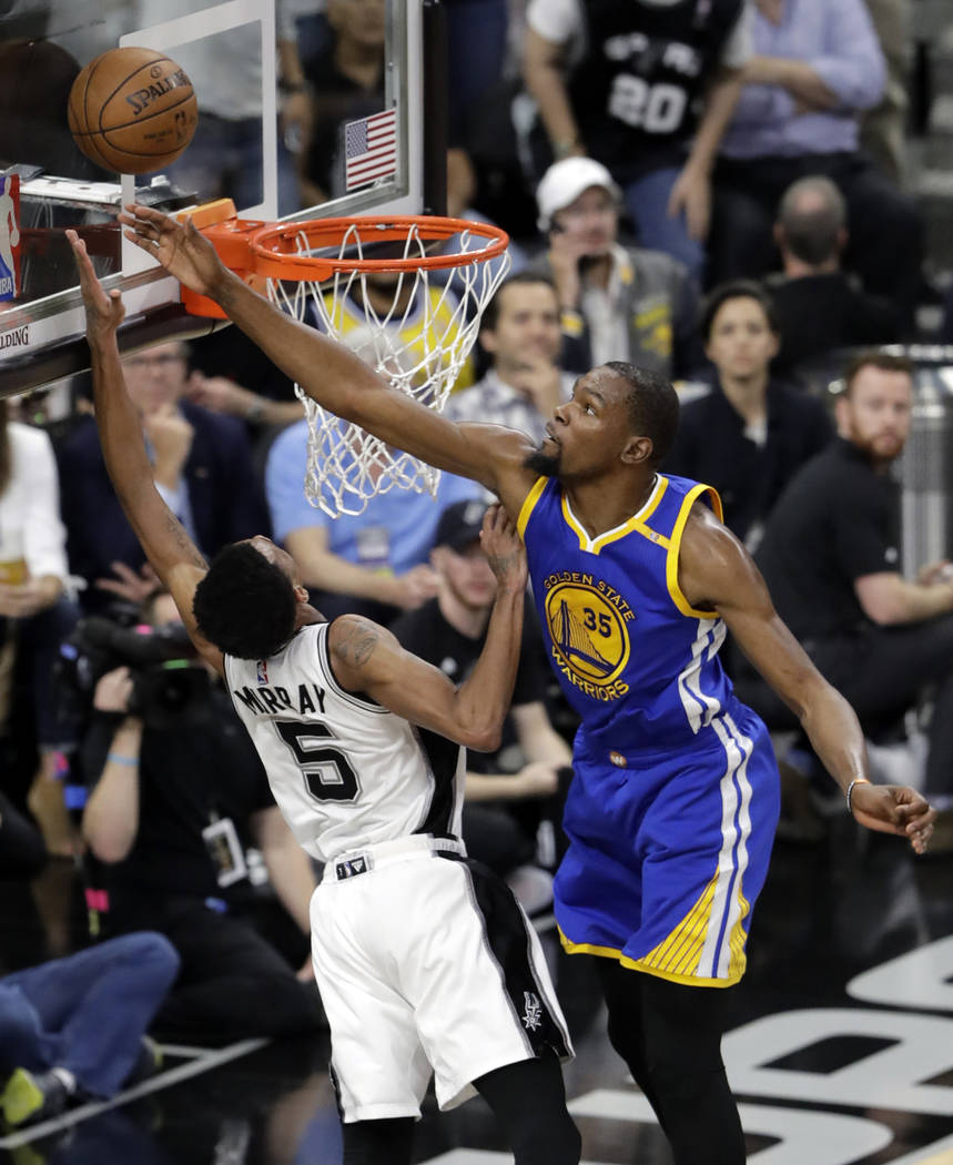 In this May 22, 2017, file photo, San Antonio Spurs guard Dejounte Murray (5) has his shot blocked by Golden State Warriors' Kevin Durant (35) during the first half in Game 4 of the NBA basketball ...