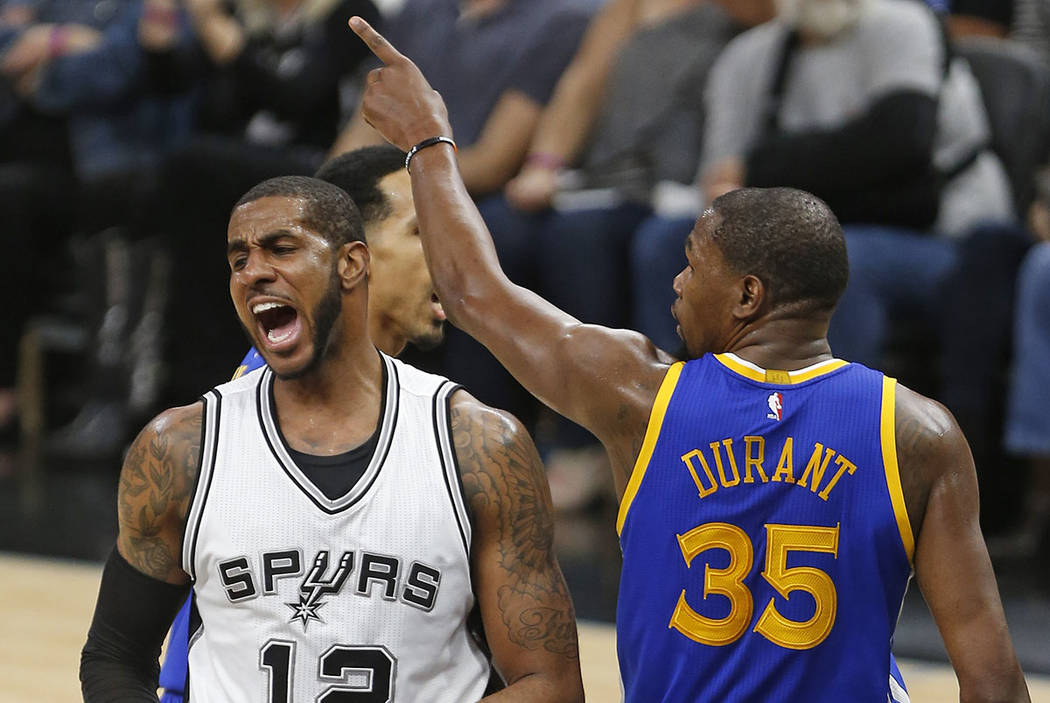 San Antonio Spurs forward LaMarcus Aldridge(12) reacts after missing a shot as Golden State Warriors forward Kevin Durant (35) gestures during the first half in Game 3 of the NBA basketball Wester ...