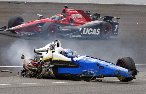 Scott Dixon, of New Zealand, sits in the remains of his car after going airborne in a crash during the running of the Indianapolis 500 auto race at Indianapolis Motor Speedway, Sunday, May 28, 201 ...