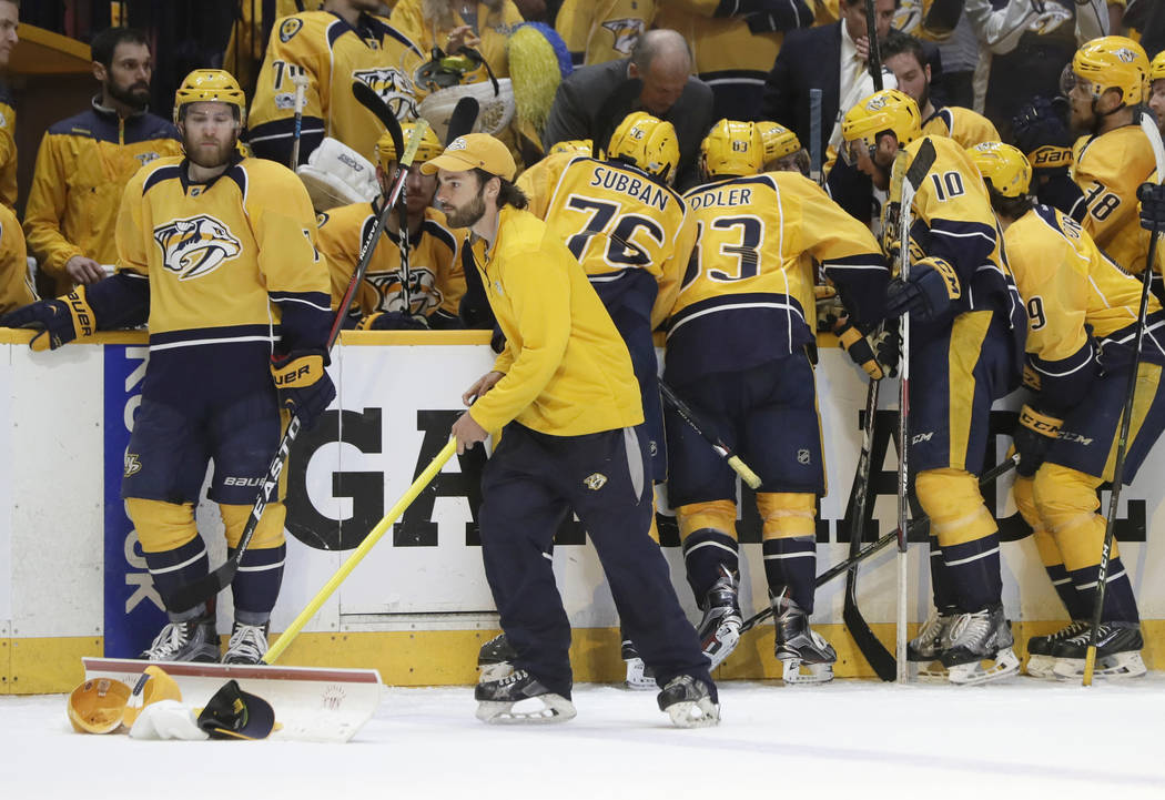 A worker cleans up hats tossed onto the ice during the third period in Game 6 of the Western Conference final after Nashville Predators center Colton Sissons (10) scored a hat trick against the An ...
