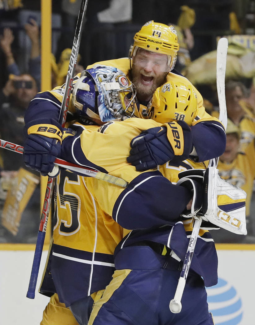 Nashville Predators defenseman Mattias Ekholm (14), of Sweden, jumps on goalie Pekka Rinne (35), of Finland, and left wing Viktor Arvidsson (38), of Sweden, after the Predators beat the Anaheim Du ...