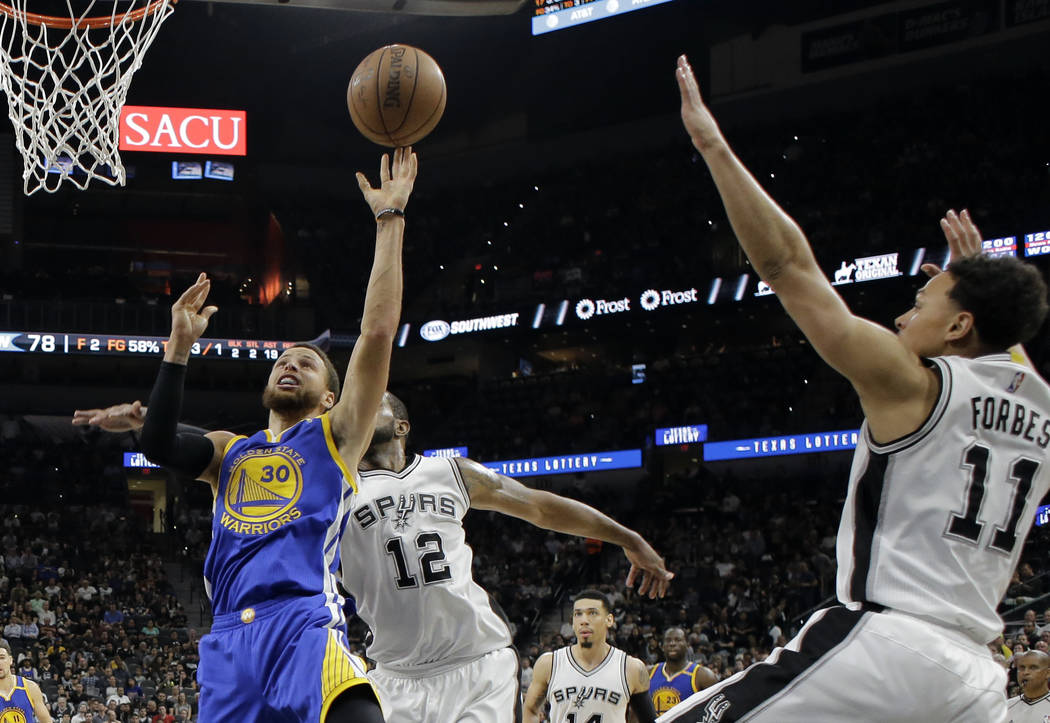 Golden State Warriors guard Stephen Curry (30) goes up for a shot as San Antonio Spurs' LaMarcus Aldridge (12) and Bryn Forbes (11) defend during the second half in Game 4 of the NBA basketball We ...