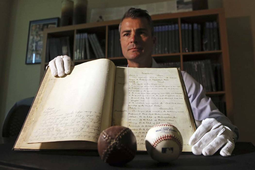 This May 18, 2017, photo shows Dan Imler, vice president of SCP Auctions, with the bound volume of the 1876 constitution that founded the National League of Professional Base Ball and the modern b ...