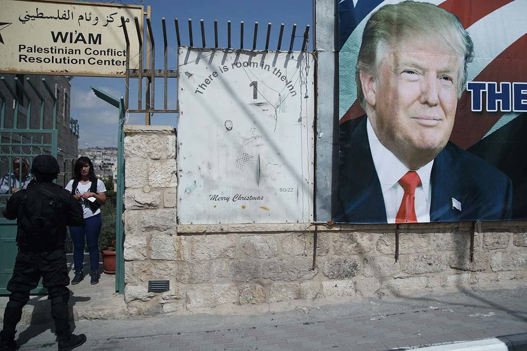 A woman watches a motorcade carrying President Donald Trump to a meeting with Palestinian President Mahmoud Abbas, Tuesday, May 23, 2017, in the West Bank City of Bethlehem. (Evan Vucci/AP)