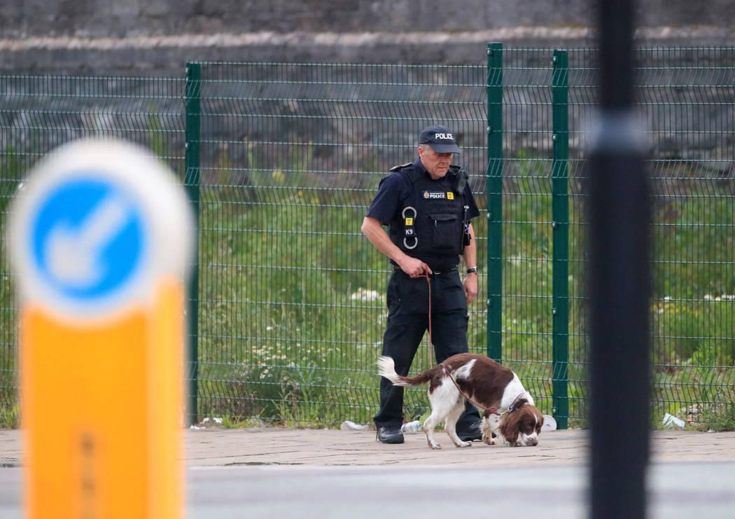 A police officer with a sniffer dog patrols near the Manchester Arena in Manchester, England Tuesday, May 23, 2017. An explosion struck an Ariana Grande concert attended by thousands of young musi ...