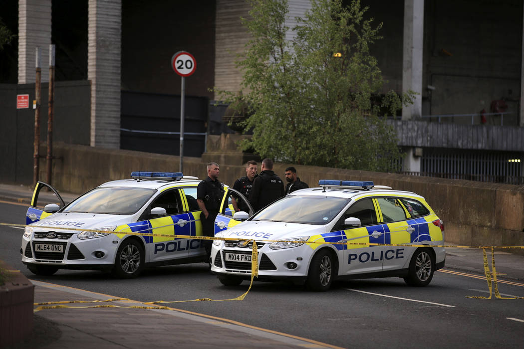 Police officers stand next to their vehicles near the Manchester Arena after a blast at Ariana Grande concert Tuesday May 23, 2017. An explosion struck the concert attended by thousands of young m ...