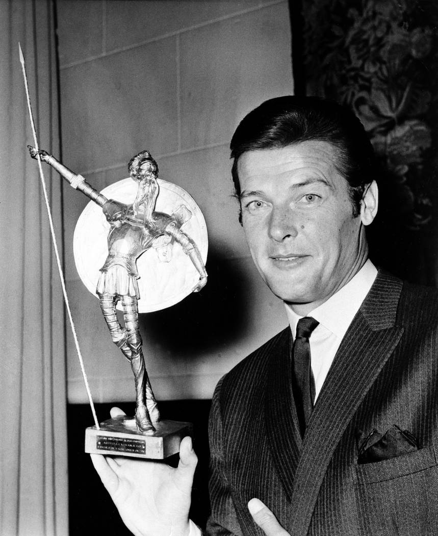 British actor Roger Moore  poses with Spain's most prized award, the Don Quixote Award, which was presented to him at the Spanish Embassy in London, July 8, 1968. (AP)