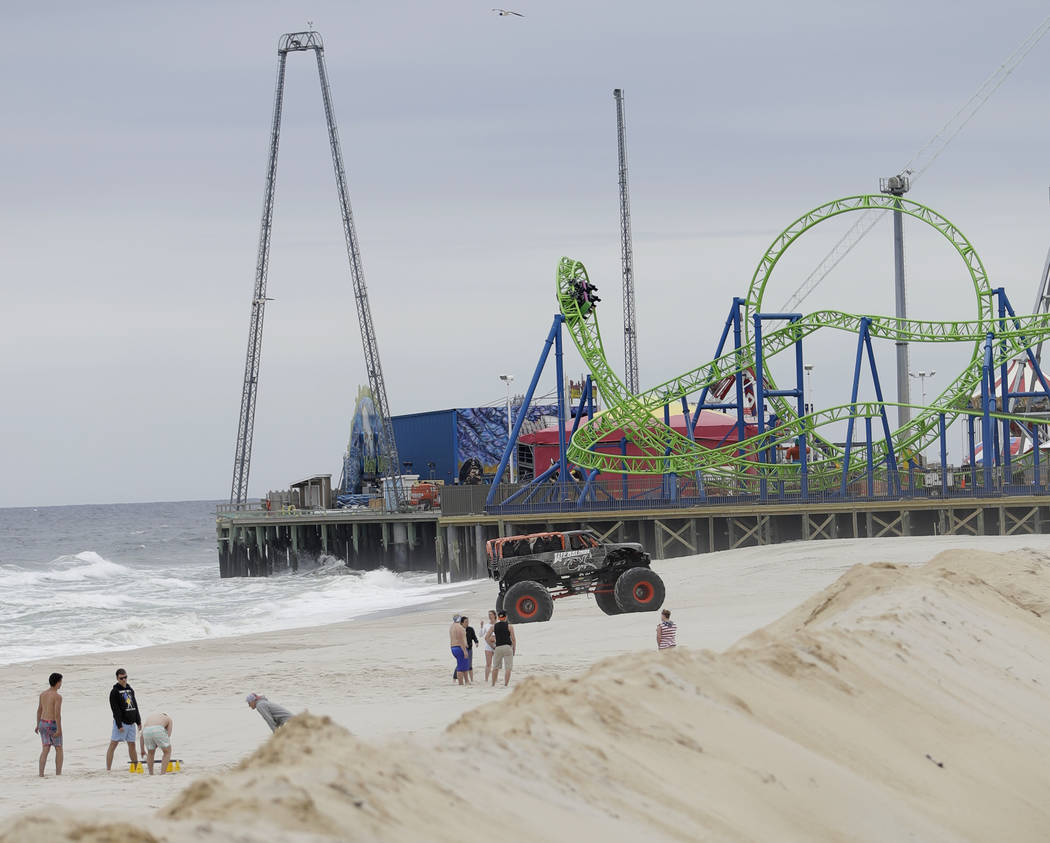 People enjoy beachside games as a a wagon from the Hydrus roller coaster, top right, goes over a turn at Casino Pier in Seaside Heights, N.J. on May 20, 2017. (Julio Cortez/AP)