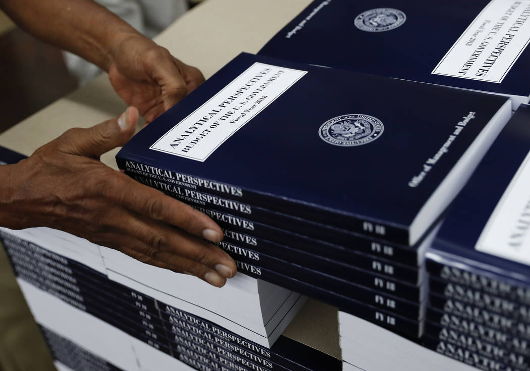 "A Government Publishing Office worker stacks copies of ""Analytical Perspectives Budget of the U.S. Government Fiscal Year 2018"" onto a pallet at the  GPO plant in Washington, May 19, 2017. (Caroly ..."