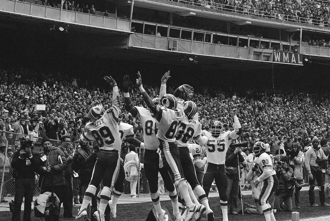 FILE - In this Jan. 8, 1983, file photo, members of the Washington Redskins celebrate after Alvin Garrett (89) scored against the Detroit Lions, in Washington. Also shown are Charlie Brown (87), C ...