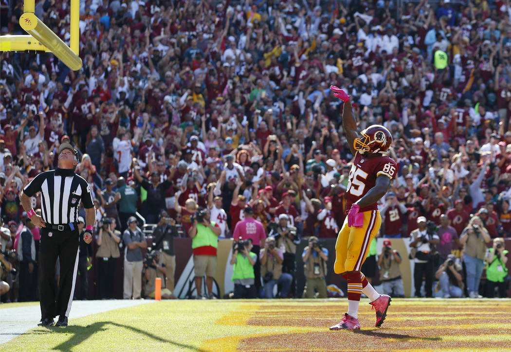 FILE - In this Oct. 16, 2016, file photo, Washington Redskins tight end Vernon Davis tosses the football through the goal posts to celebrate scoring a touchdown in the first half of an NFL footbal ...