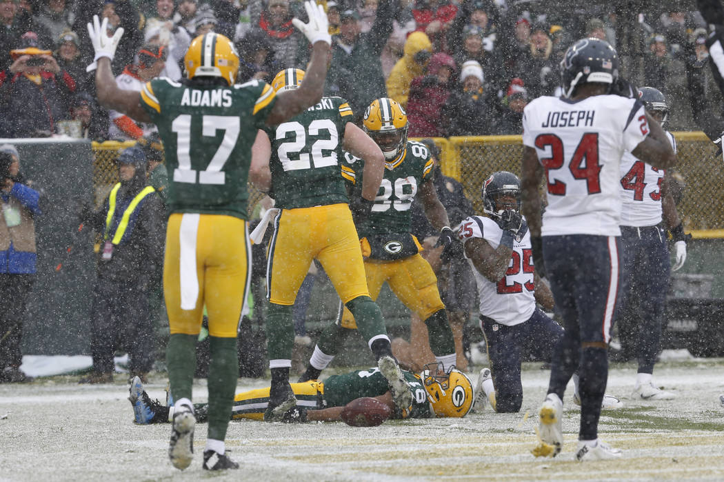 FILE - In this Dec. 4, 2016, file photo, Green Bay Packers' Randall Cobb makes a snow angel after catching a touchdown pass during the first half of an NFL football game against the Houston Texans ...