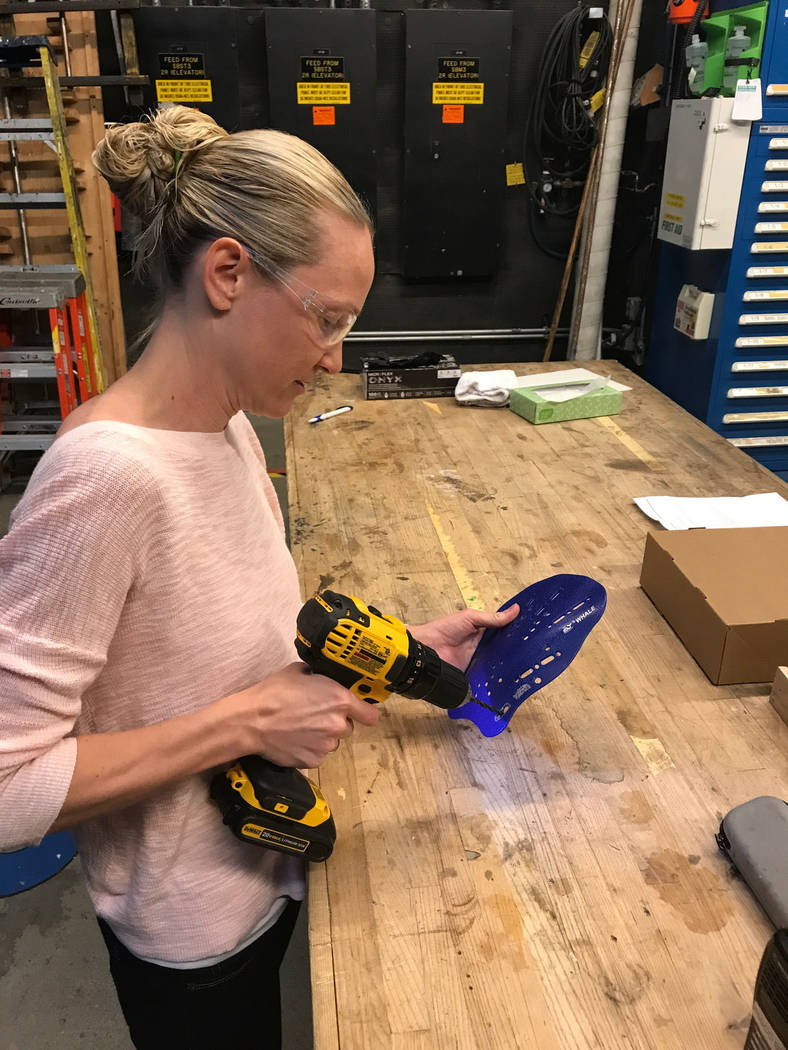 Brynn Coseru, a Cirque du Soleil synchronized swimmer, creates the hand fins she made as part of the requirements for her master's degree in occupational therapy degree at Touro University.  Photo ...
