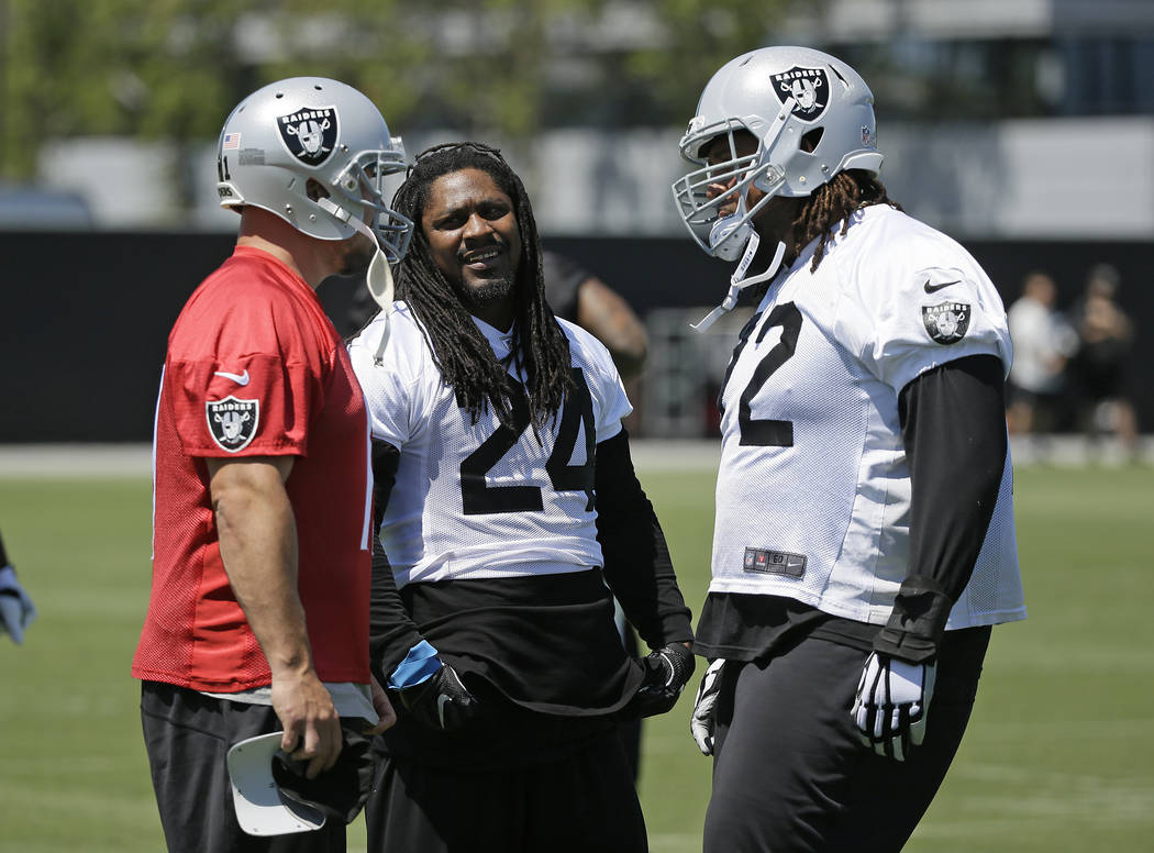 Oakland Raiders running back Marshawn Lynch, center, talks with kicker Sebastian Janikowski, left, and tackle Donald Penn, right, during an NFL football team activity Tuesday, May 23, 2017, in Ala ...