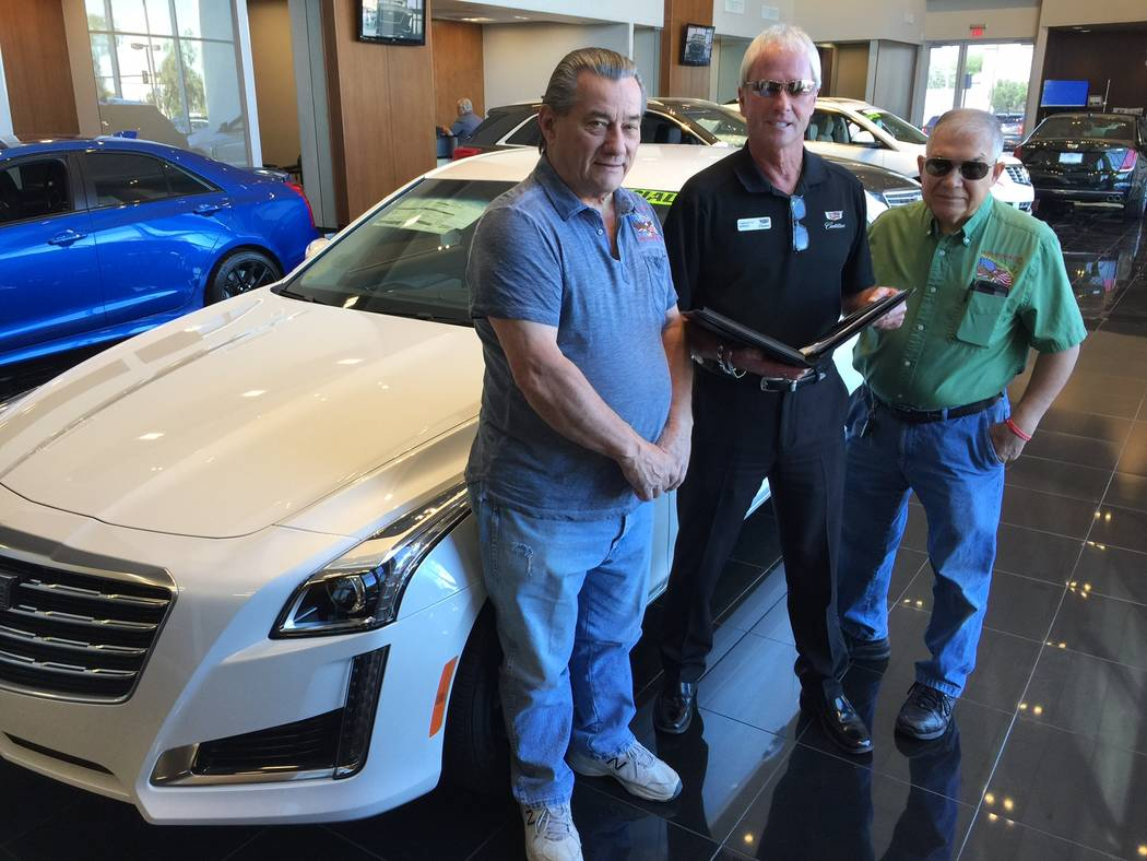 Findlay Findlay Cadillac marketing director L.J. Harness, center, is flanked by Veterans Transition Resource Center COO Jim Lytner, left, and VTRC media services director R.J. Dough as the three p ...