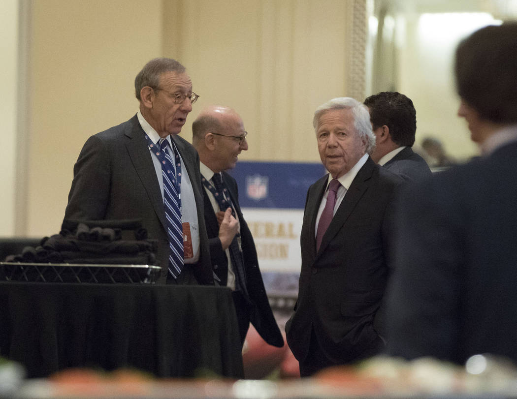 Miami Dolphins owner Stephen Ross, left, speaks to New England Patriots owner Robert Kraft, right, at the NFL owners meeting at the JW Marriott hotel in Chicago, Ill., on Tuesday, May 23, 2017. (H ...