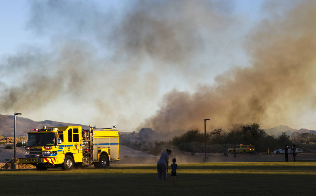 People watch as Clark County firefighters respond to a brush fire at Sunset Park in Las Vegas on Tuesday, May 23, 2017. Chase Stevens Las Vegas Review-Journal @csstevensphoto