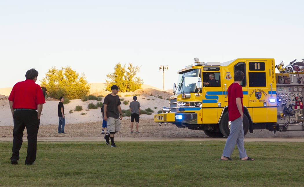 A Clark County fire engine passes by onlookers while making a run to fill up on water as firefighters respond to a brush fire at Sunset Park in Las Vegas on Tuesday, May 23, 2017. Chase Stevens La ...