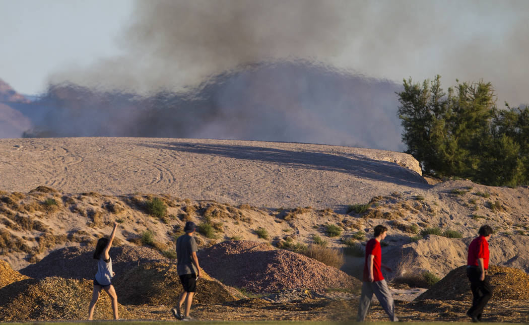 People pass by a brush fire at Sunset Park in Las Vegas on Tuesday, May 23, 2017. Chase Stevens Las Vegas Review-Journal @csstevensphoto