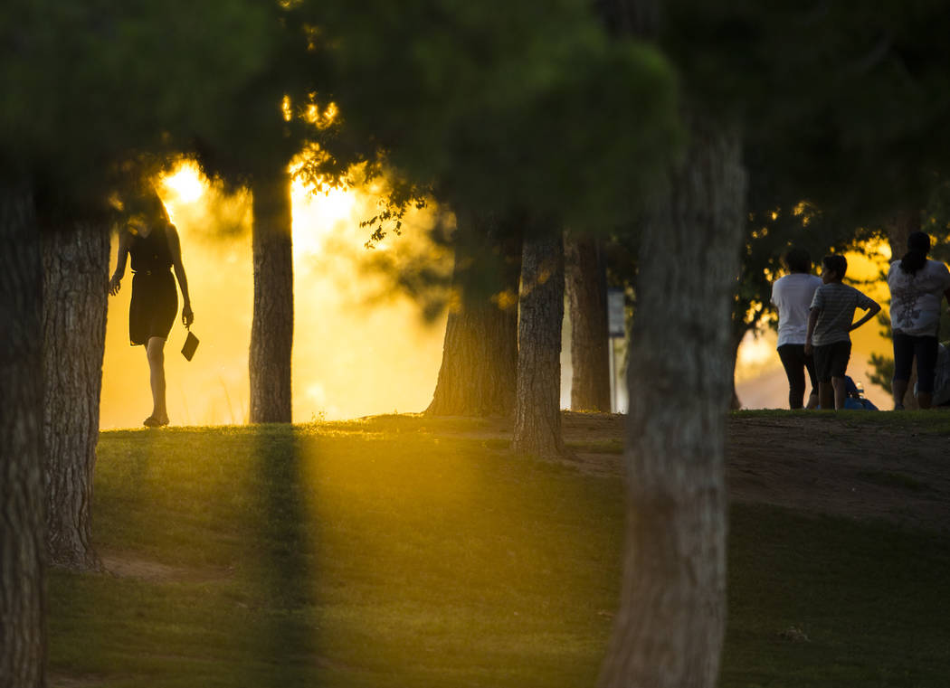 People are silhouetted as smoke from a brush fire passes through Sunset Park in Las Vegas on Tuesday, May 23, 2017. Chase Stevens Las Vegas Review-Journal @csstevensphoto
