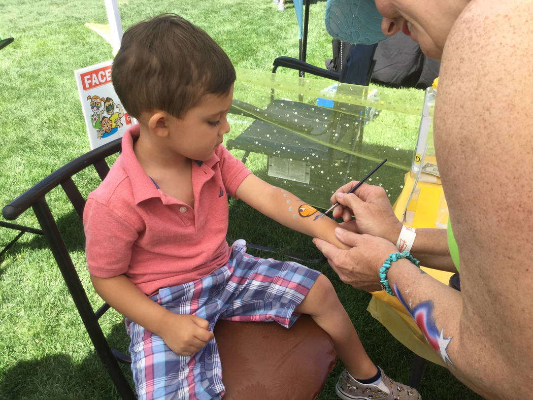 Carrie Hebert of Giggle Facepainting paints a fish on 3-year-old Kovu Morabbi at the Best Dam Barbecue Challenge on Saturday in Boulder City (Bailey Schulz Las Vegas Review-Journal)